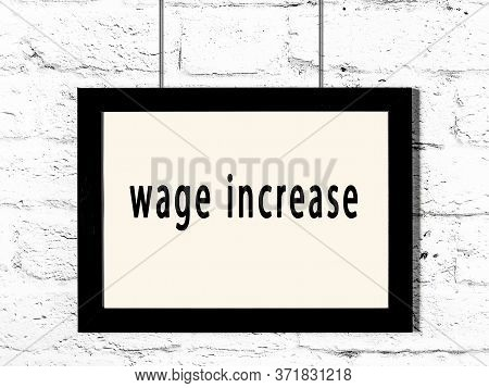 Black Wooden Frame With Inscription Wage Increase Hanging On White Brick Wall