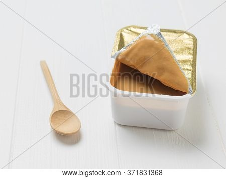 A Wooden Spoon And An Open Container Of Peanut Paste On A White Table. Natural Peanut Cream.