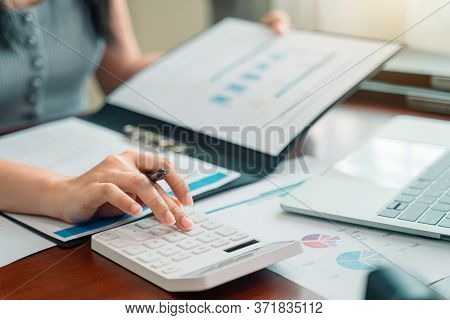 Businesswoman Working On Calculator To Calculate Business Data Financial Report On Wooden Table. Bus