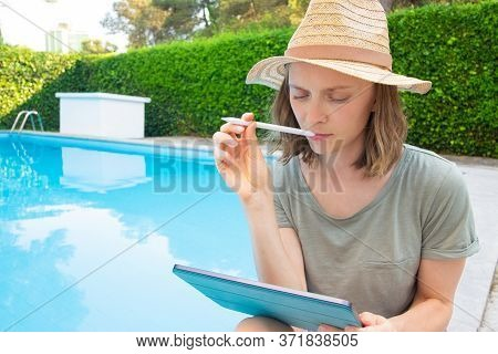 Pensive Creative Freelancer With Tablet Biting Pen, Thinking Over Ideas While Sitting And Working At
