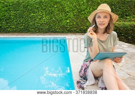 Positive Relaxed Woman Sitting At Swimming Pool, Using Tablet And Stylus, Looking At Camera. Outdoor