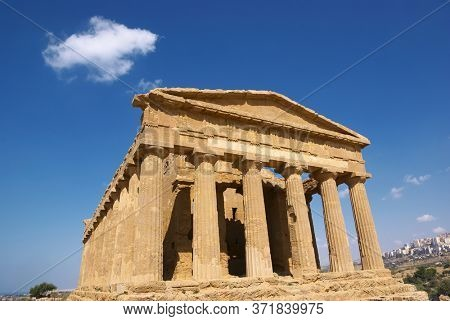temple of Concordia and white cloud in the Valley of Temples in Agrigento, a Sicily landmark of Unesco architecture