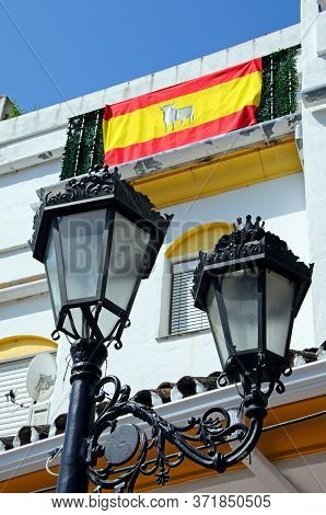 Wrought Iron Streetlight With A Spanish Flag On Townhouse Balcony To The Rear, Pueblo Blanco, Benaha