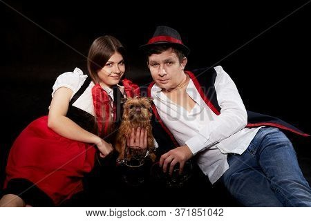 Happy Oktoberfest Couple In National Ethnic Dress With Mug Of Beer, Small Shaggy Dog Resting On Blac