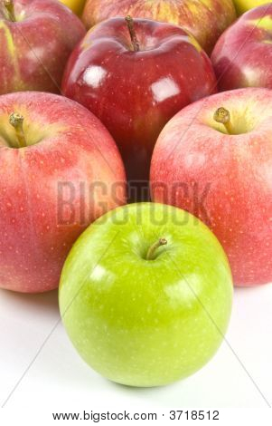 One Granny Smith apple in front of a bunch of pink apples. poster