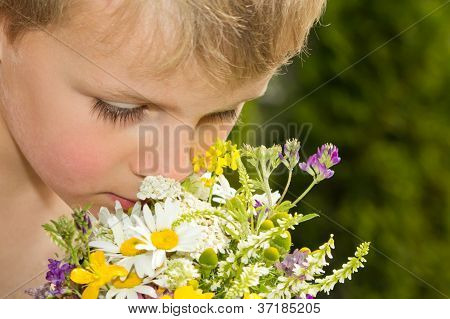 Young Boy Smelling Bouquet Of Wildflowers