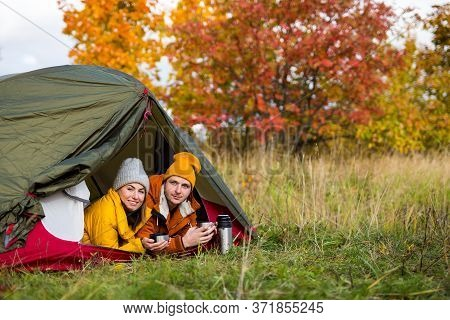 Travel, Trekking And Hiking Concept - Portrait Of Young Couple Drinking Tea Or Coffee In Tent In Aut