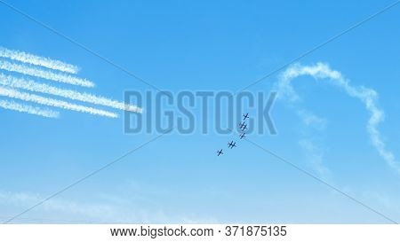 Airplanes On Airshow. Aerobatic Team Performing Flight At Air Show, Drawing Lines On Blue Sky.