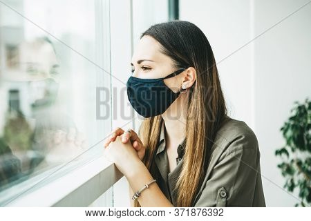 A Sad Girl In A Face Mask Looks Out The Window From Home.