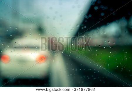 Rain Drops On Windshield. Car Driving On Asphalt Road On Rainy Day. Windshield Window Of Car With Ra