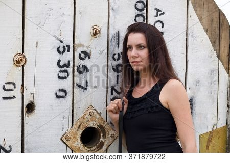Girl Posing Near A Wooden Reel For Cable. On The Shoulder Is A Handbag.