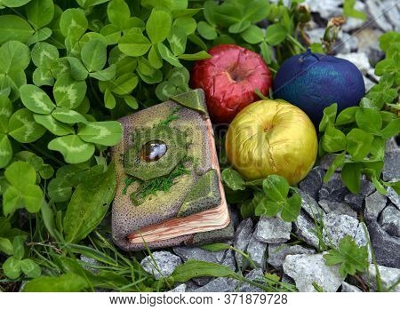 Fairy Tale Book And Three Magic Apples Outdoors In The Garden. Esoteric, Gothic And Occult Backgroun