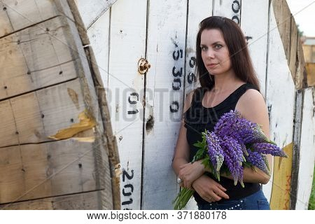 Woman With A Bouquet Of Lupine In Her Hands. It Stands On The Background Of Wooden Reels For Cable.