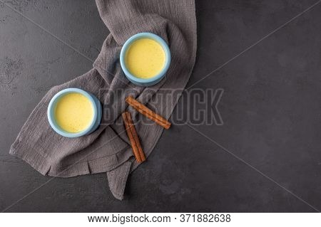 Two Blue Cups With Traditional Indian Masala Chai Tea And Cinnamon Sticks On A Linen Napkin On A Dar