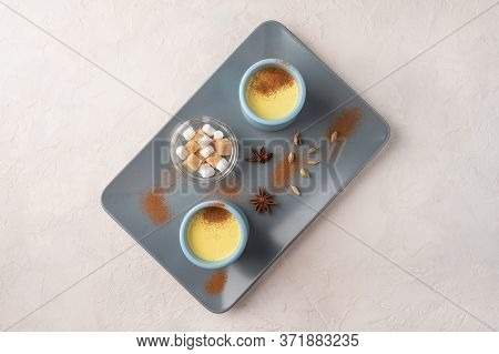Two Blue Cups With Traditional Indian Masala Chai Tea With And Sugar On A Ceramic Tray On A Light Ba