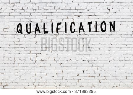 Word Qualification Written With Black Paint On White Brick Wall.