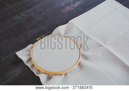Canvas For Embroidery With A Cross Embroidered In A Round Wooden Hoop Lies On A Dark Table