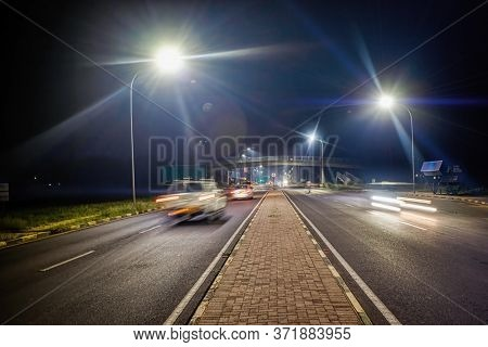 A bridge over the main road in the night, traffic on the  streets of Gaborone