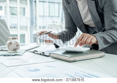 Business Woman Uses A Calculator To Calculate Financial Graphs That Show Results And Analyze Financi