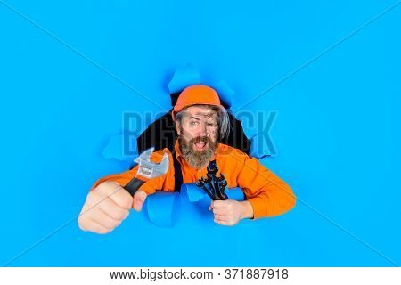 Bearded Builder Look Through Paper. Adjustable Wrench. Worker In Helmet. Worker Holds Wrenches. Wren
