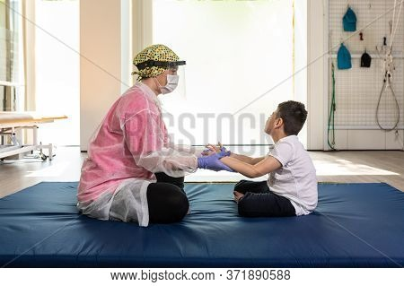 Child Patient And Female Physiotherapist In Rehabilitation Session, Exercises On Mat During Coronavi