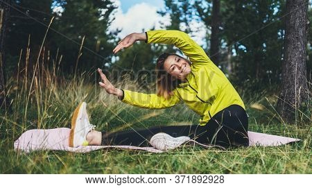 Smile Girl Exercising Outdoors In Green Park, Activity With Stretch Arms And Legs. Young Fitness Wom