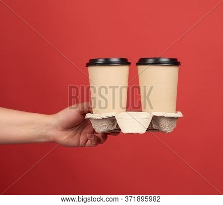 Brown Paper Disposable Cups With A Plastic Lid Stand In The Tray, Female Hand Holds Disposable Table
