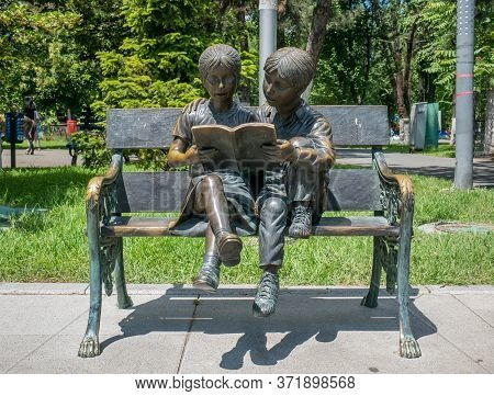 Bucharest/romania - 05.30.2020: Bronze Statue Of A Girl And A Boy Reading A Book On A Bench.