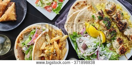 greek meal with chicken souvlaki platter, gryos, french fries, salad and baklava