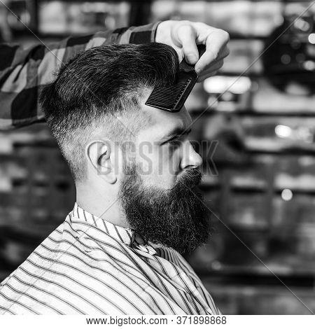 Bearded Man Getting Haircut By Hairdresser. Brutal Guy Sitting In Barber Chair. Vintage Barbershop,