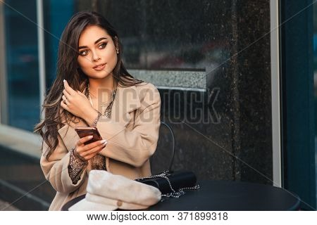 Fashionable Girl With Mobile Phone Sitting At Cafe Outdoors. City Lifestyle. Women Fashion. Woman Wi