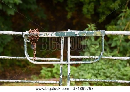 Metal Gate Closed Outside With A Padlock And Chain