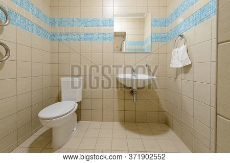 Toilet Apartment Interior. Toilet Bowl In The Toilet Room. Restroom With Beige Tile Decoration And F