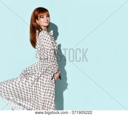 Young Pretty Smiling Red-haired Woman In Elegant Flying Light Dress Standing Side To Us And Looking