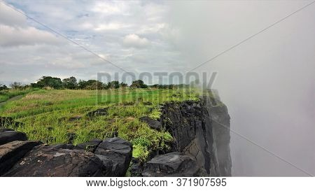 Victoria Falls, Zambia. The Plateau, Covered With Bright Green Grass, Ends With A Vertical Cliff Int