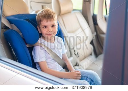 Little Caucasian Boy Sits In A Blue Child Safety Seat. Traveling With A Child In A Car With A Leathe