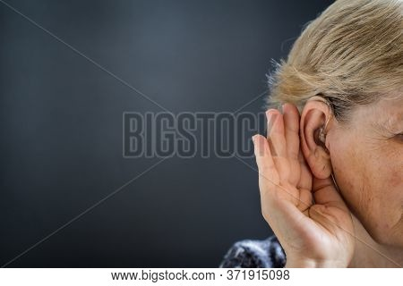 Old Woman With Hearing Aid On Black-gray Background. Hearing Loss And Deafness Concept.