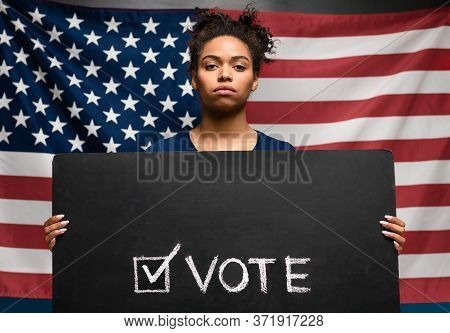 Presidential Elections 2020 In Usa. Black Woman Holding Vote Sign Against American Flag