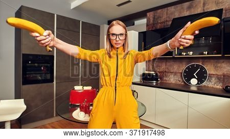 Pretty funny young woman pretends to shoot bananas at home in the kitchen. Modern interior, furniture for the kitchen. Cook at home. Healthy eating and diet.