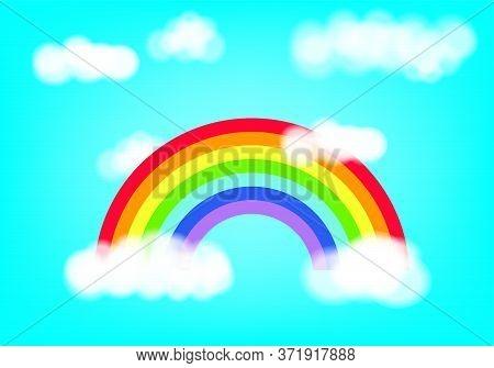 Classic Cartoon Rainbow Arc With Clouds Against Blue Sky Background. Vivid Spectrum. Color Pride Har