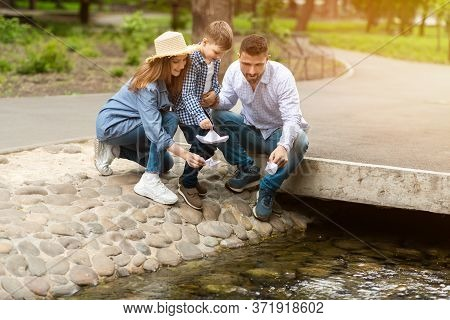 Happy Boy With His Parents Launching Paper Boat In Small Brook At Park