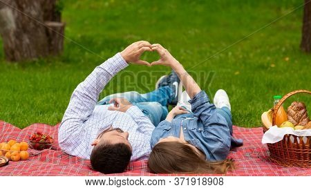 Young Loving Couple Making Hearts With Their Hands While Lying On Picnic Blanket Outdoors, Panorama