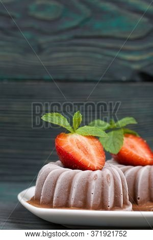 Chocolate Fudge Garnished With Half A Strawberry With Petals. Saucer With Dessert Stands On Brushed