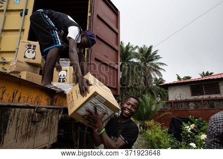 Lunsar, Sierra Leone - June 9, 2015: Two African Happy Men Help Unload A Trailer With Humanitarian A