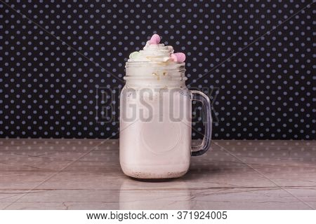 Sweet Milkshake In A Square Mug And Whipped Cream On Marble Table Background. Fresh Tasty Cocktail O