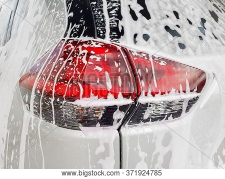 Car Taillight On Back Lid Covered With Active Foam For Washing A Dirty Car And  Wax, Close Up Of The