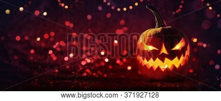 Halloween Pumpkins Glowing In Fantasy Night. Jack O'Lantern Holiday Horror Background