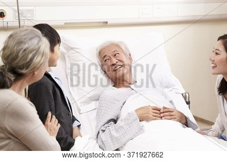 Senior Asian Old Man Lying In Hospital Bed Getting A Visit From Family