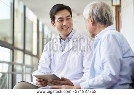 Friendly Smiling Young Asian Doctor Talking And Explaining Test Result To Elderly Patient In Hospita