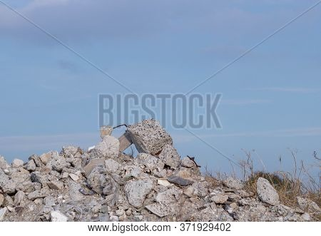 A Large Pile Of Sandy Soil With A Stone. Above, You Can See Blue Sky And White Clouds. Construction.